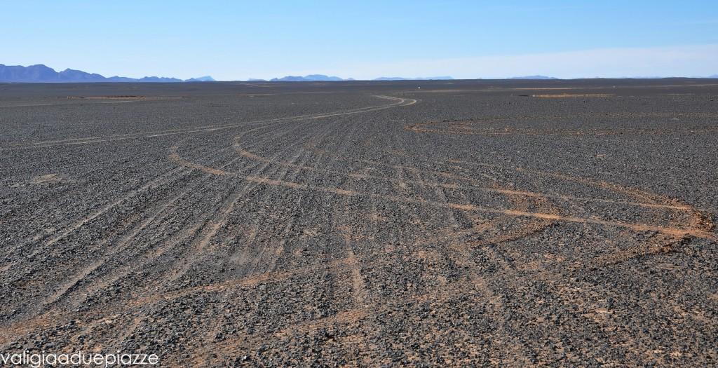 A poco a poco i sassi neri si trasformano in sabbia rossa. Quello sul fondo è il Sahara.